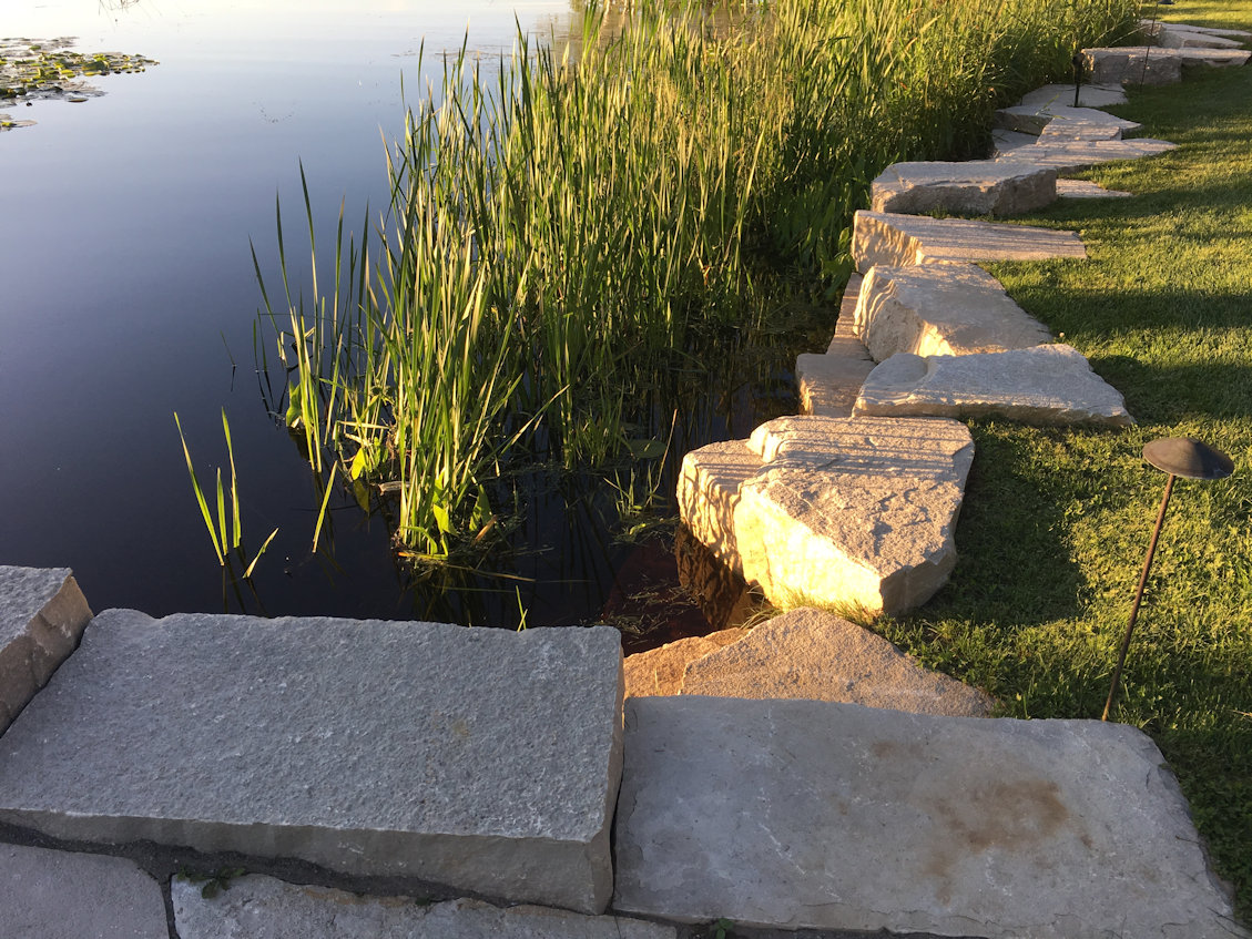 This attractive stone wall prevents erosion. The lights keep the edge visible and safe for nighttime strolls.