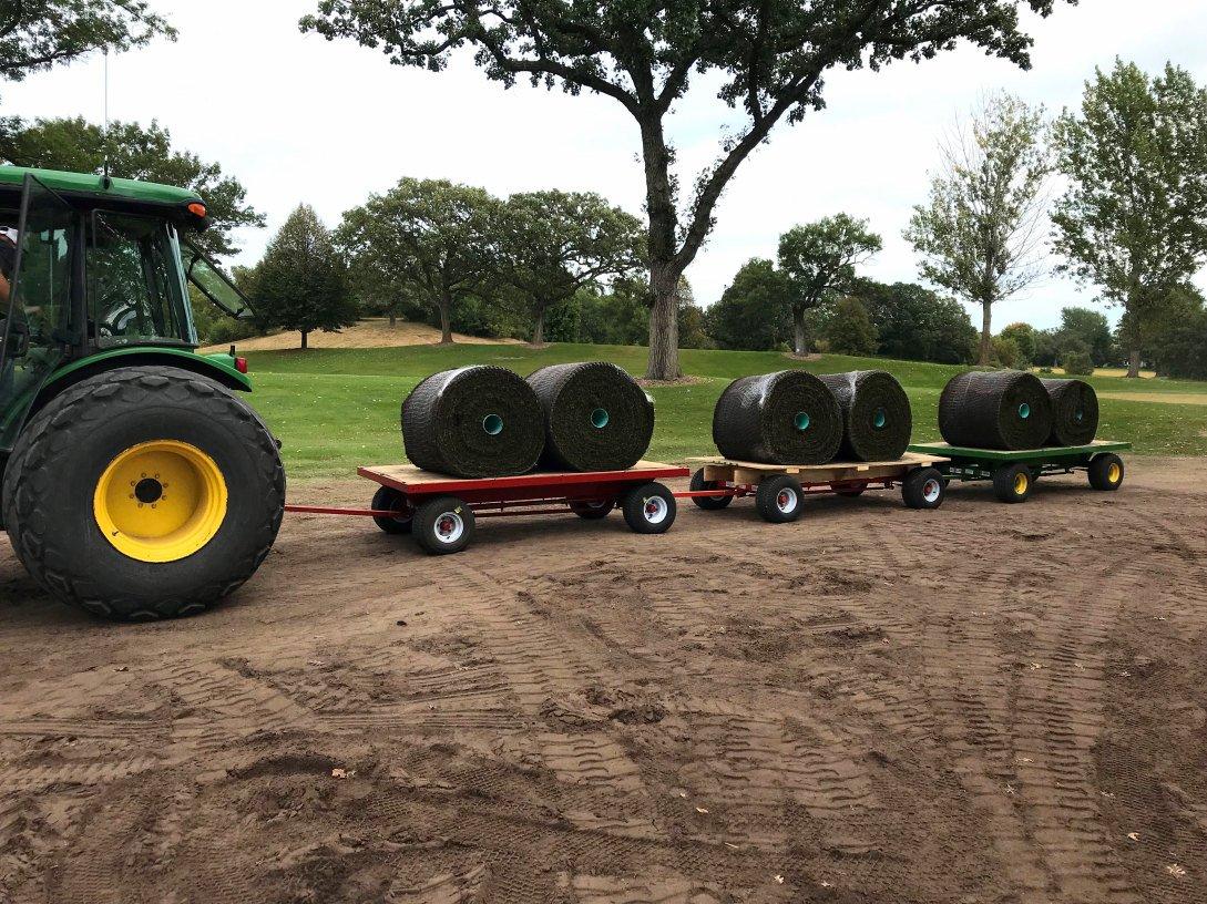 Hartman Companies staff tractors a sod train through the golf course